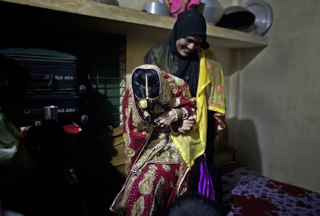 """MANIKGANJ, BANGLADESH - AUGUST 20: A relative tries to drag 15 year old Nasoin Akhter onto a bed to pose for photographs on the day of her wedding to a 32 year old man, August 20, 2015 in Manikganj, Bangladesh.  In June of this year, Human Rights Watch released a damning report about child marriage in Bangladesh. The country has one of the highest rates of child marriage in the world, with 29% of girls marrying before the age of 15, and 65% of girls marrying before they turn 18. The detrimental effects of early marriage on a girl cannot be overstated. Most young brides drop out of school. Pregnant girls from 15-20 are twice as likely to die in childbirth than those 20 or older, while girls under 15 are at five times the risk. Research cites spousal age difference as a significant risk factor for violence and sexual abuse. Child marriage is attributed to both cultural tradition and poverty. Parents believe that it """"protects"""" girls from sexual assault and harassment. Larger  dowries are not required for young girls, and economically, women's earnings are insignificant as compared to men's. (Photo by Allison Joyce/Getty Images)"""