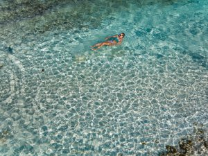 Aerial view of a woman floating in tropical Caribbean water at Lindquist Beach, St Thomas, United States Virgin Islands