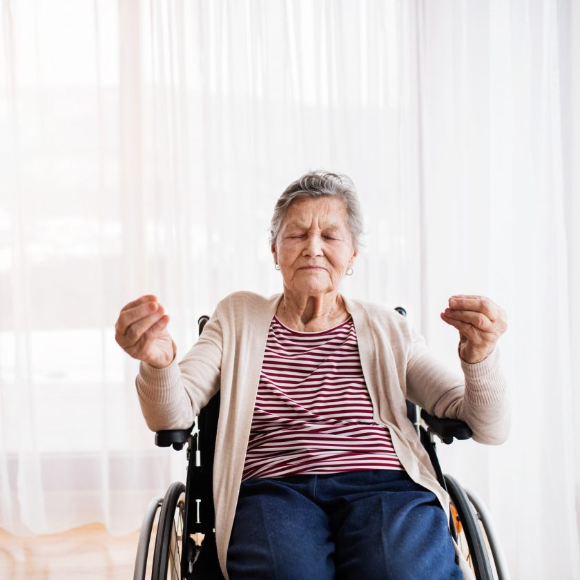 Senior woman in wheelchair at home, meditating.