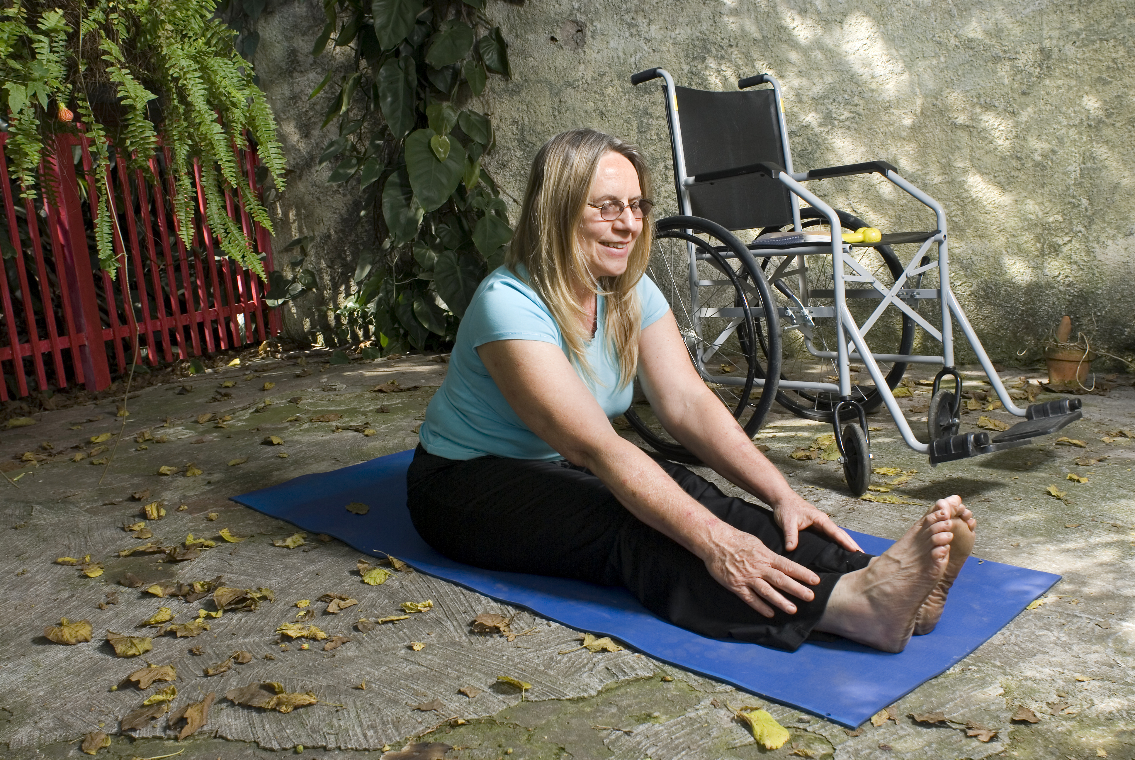 Woman,Sits,Next,To,A,Wheelchair,On,Blue,Yoga,Mat