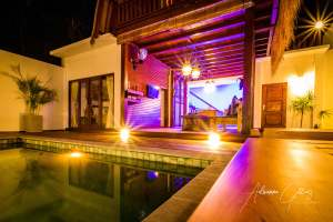 Open plan bungalow with pool and pretty purple lights at night