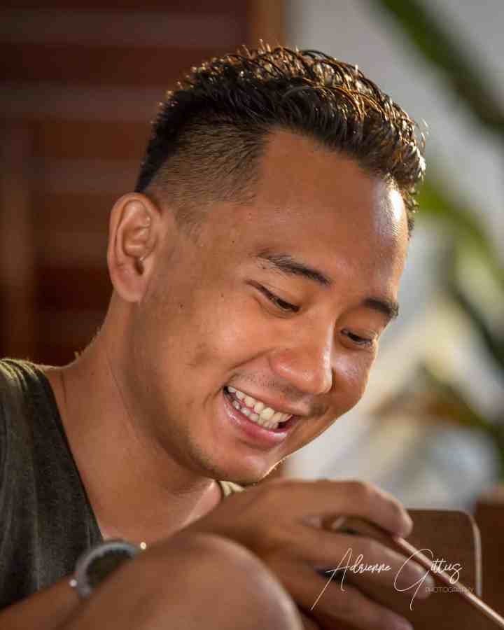 Indonesian man smiling looking at his cell phone, candid portrait, Indonesia