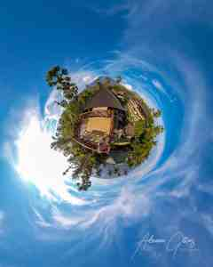 tiny planet of Vill Alba, Tulamben, Indonesia with pretty blue sky and Mt Agung at the top