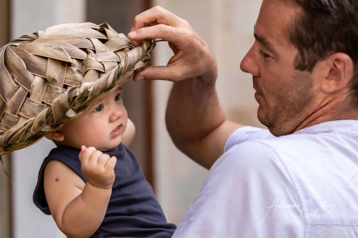 portrait gallery photo father and son playing peekaboo under a hat candid shot