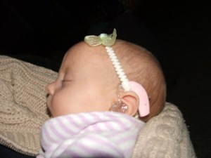 newborn baby wearing a hearing-aid