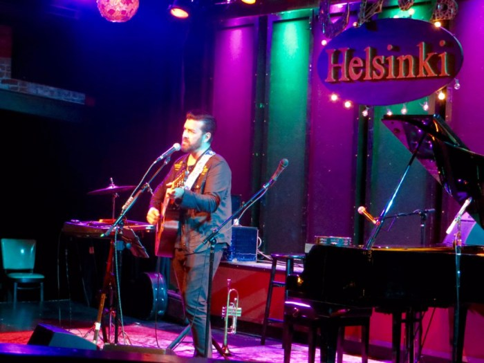 Bob Schneider singing and playing guitar on stage at Helsinki Hudson.