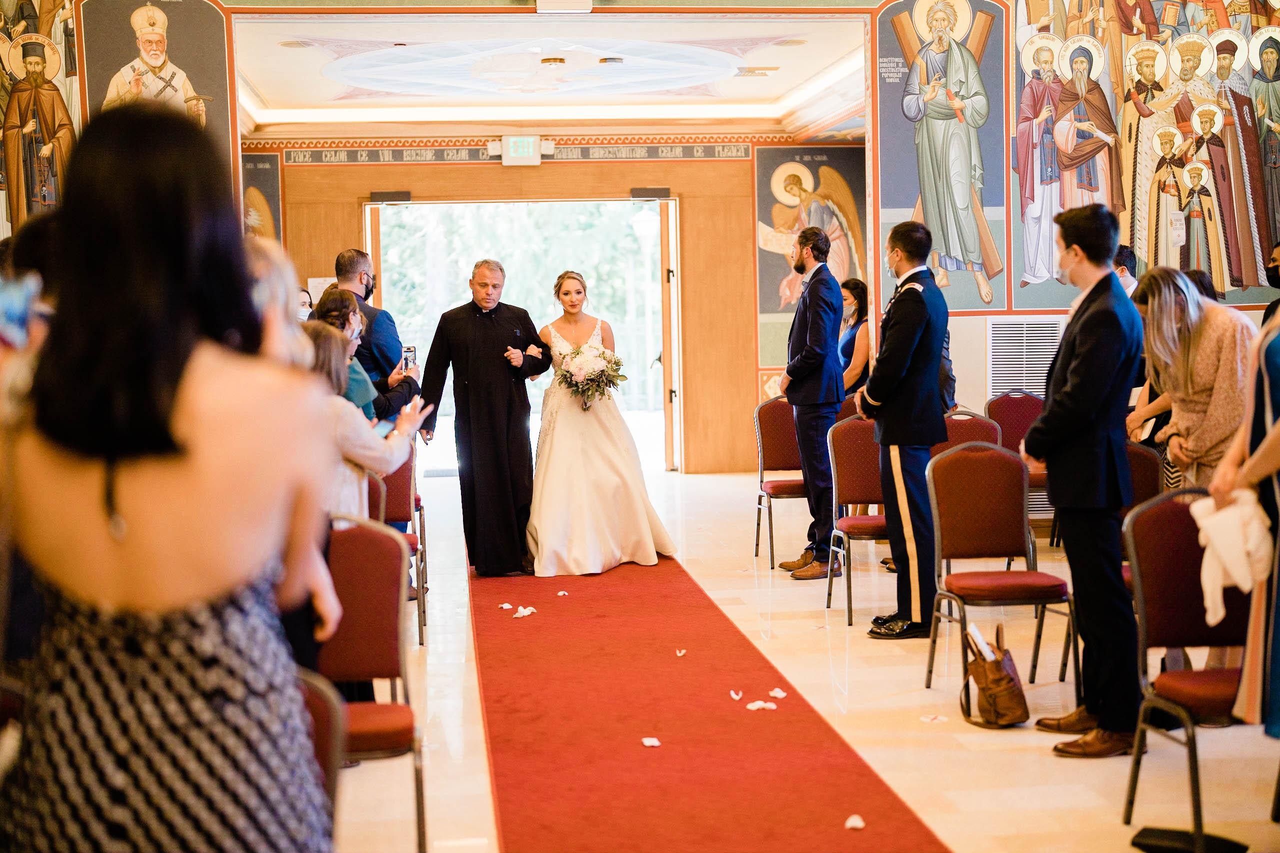 bride walks down aisle at Romanian Orthodox Church in Mountlake terrace