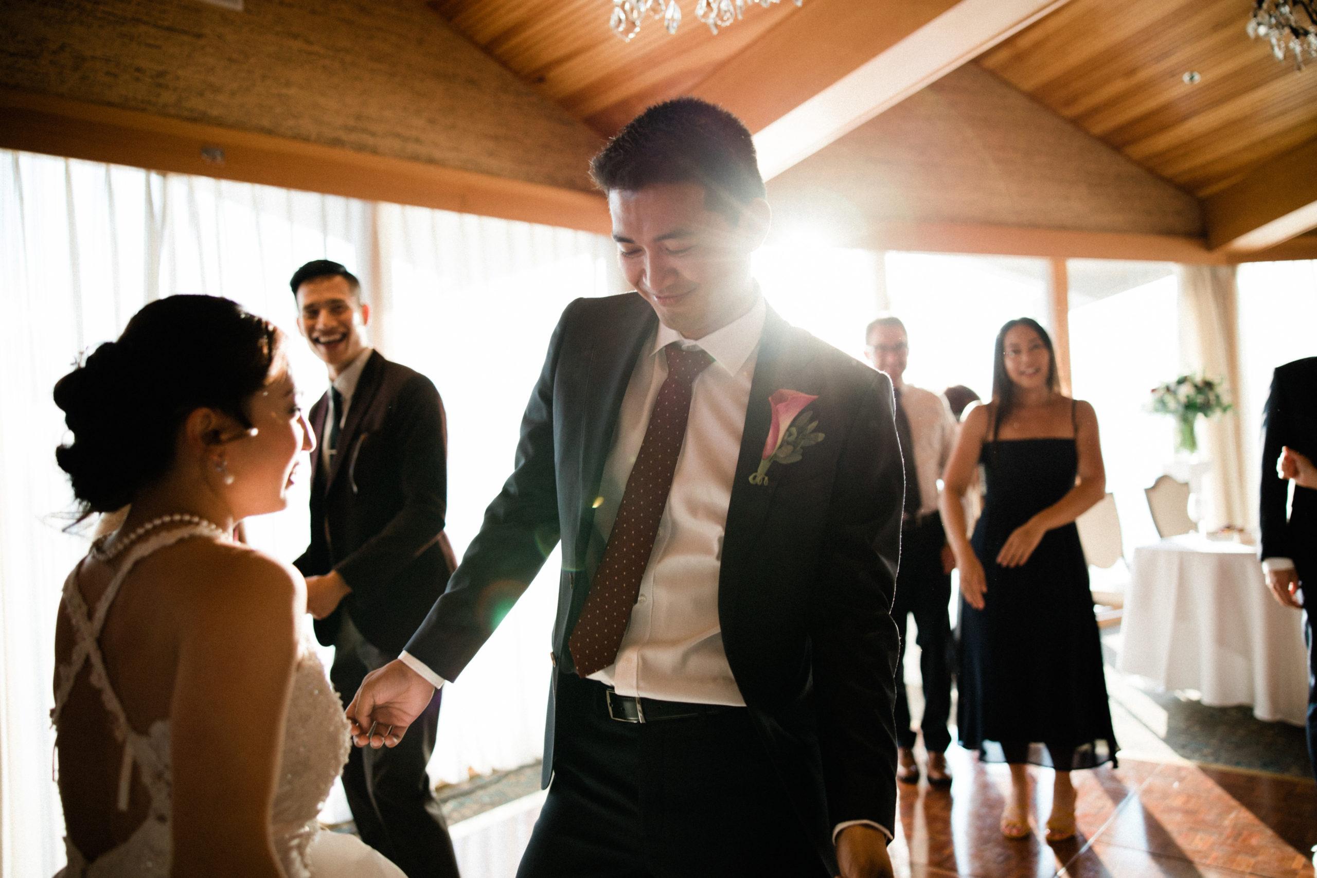 groom dances on the ballroom wood floor with guests cheering