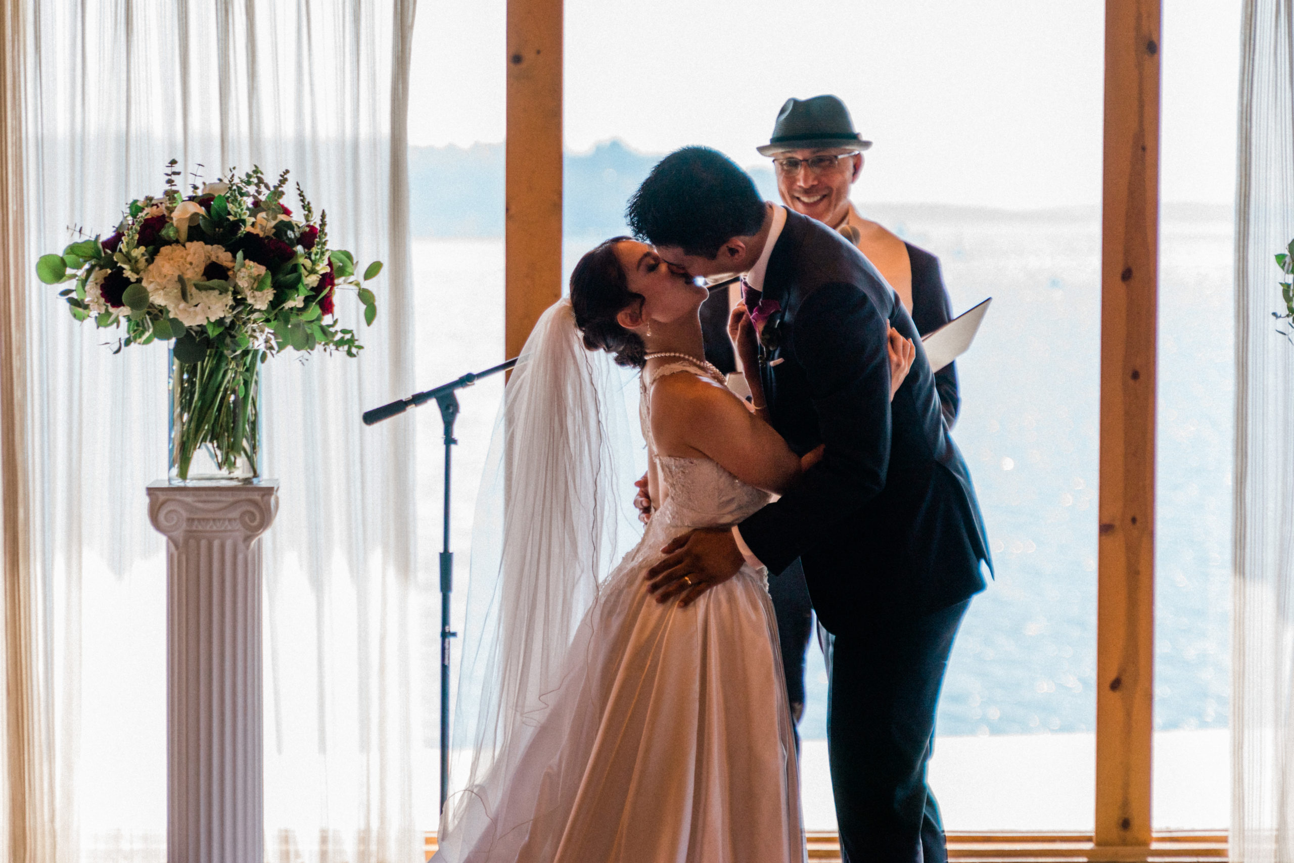 husband and wife share first kiss after being pronounced a married couple at edgewater hotel