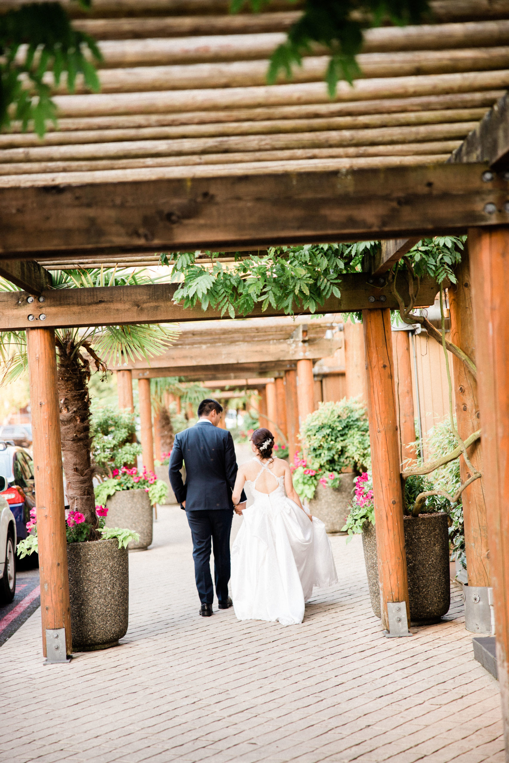 husband and wife leave edgewater hotel lobby after getting married on their way to honeymoon