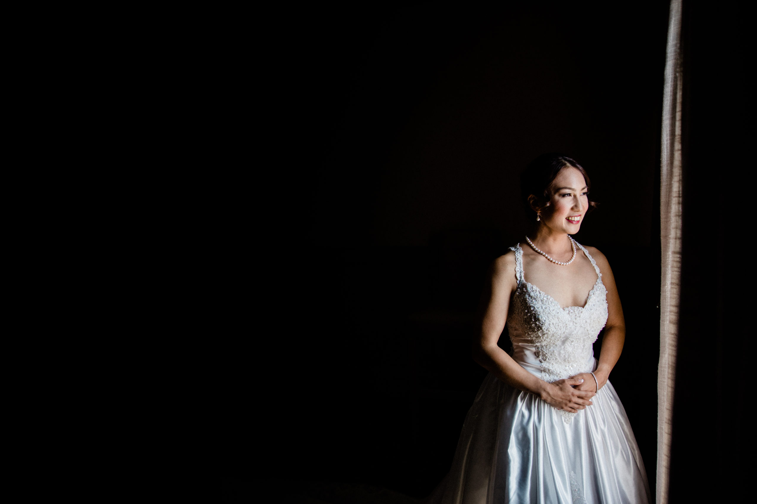 bride admires her dress in full length mirror in bridal suite at edgewater hotel photos
