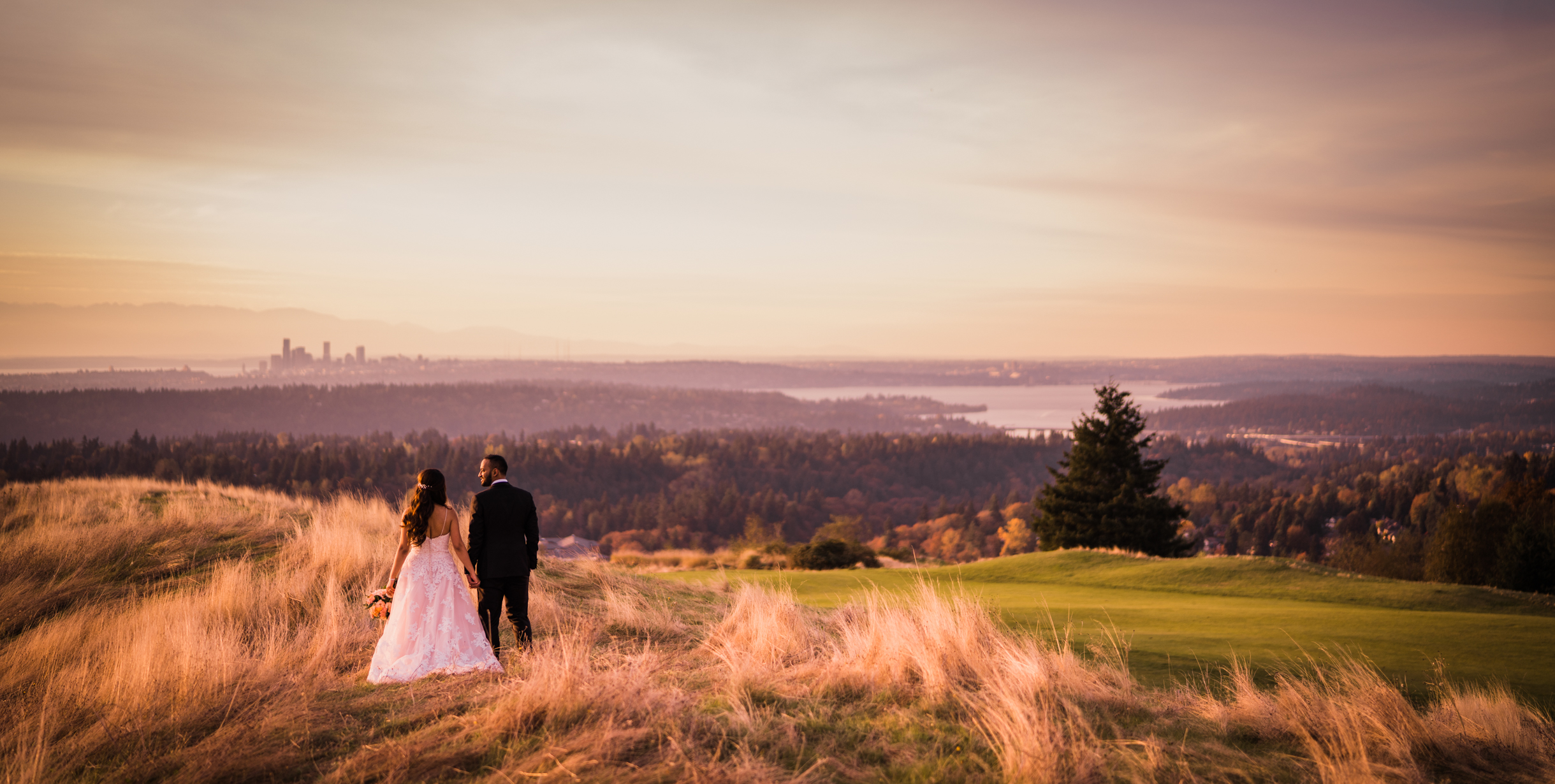 bride and groom stand on golf course with seattle skyline for romantic images