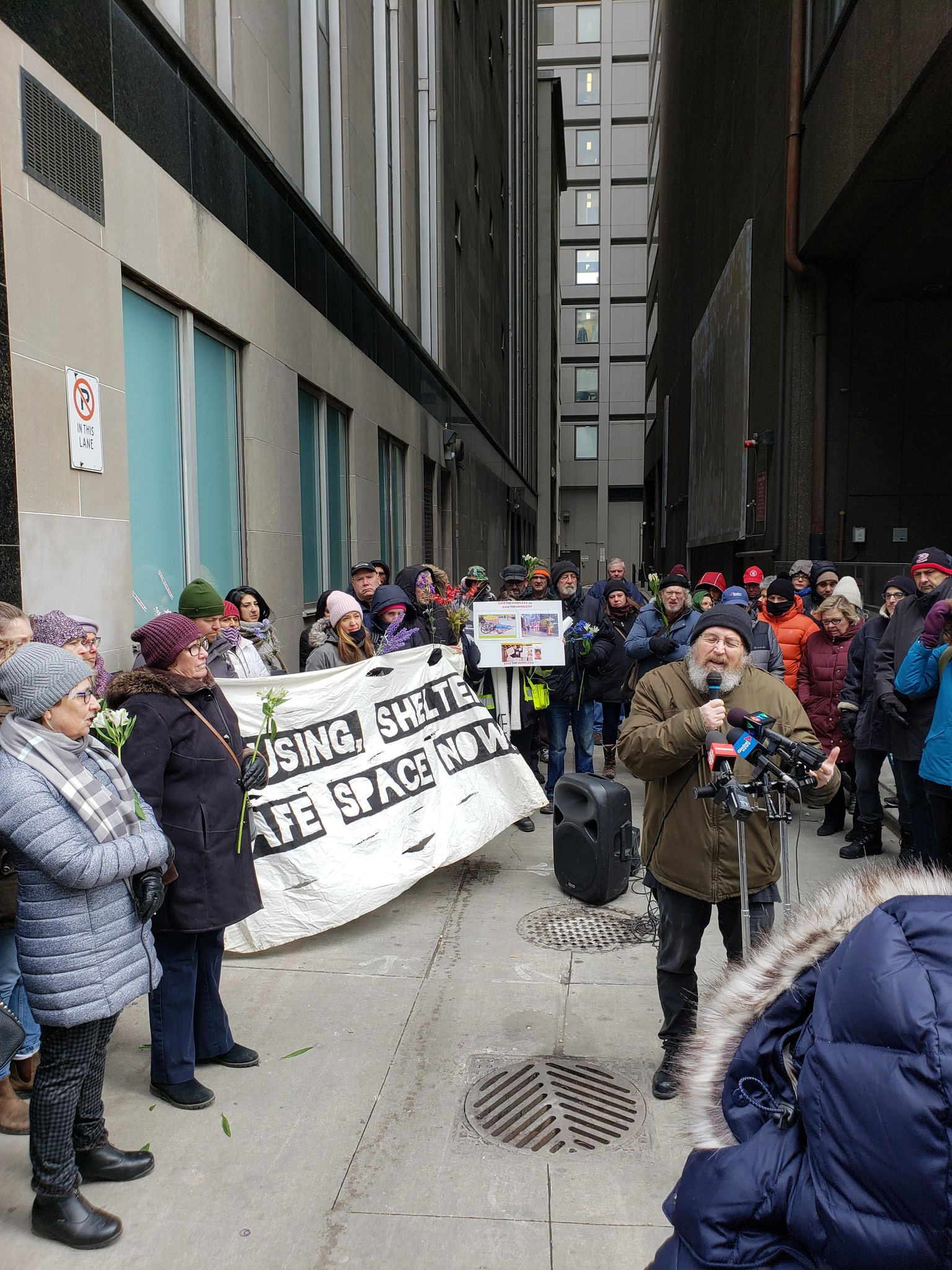 "Outdoor rally in an alley with a man speaking into a microphone and a large sign with text ""Housing Shelter Safe Space Now""."