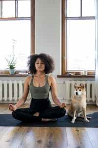 woman meditating seated next to a dog