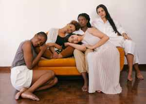photo of women from diverse backgrounds sitting on orange sofa. Women's health is important to all of them.
