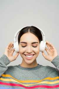 woman in gray sweater wearing white headphones listening to music playlists