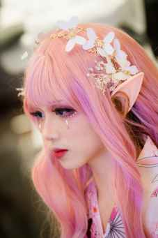 a female-appearing teen wearing elf ear and floral headdress is engaging in adolescent identity development through cosplay