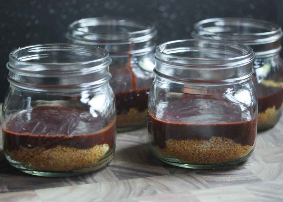 Four s'mores in a jar, ready for baking