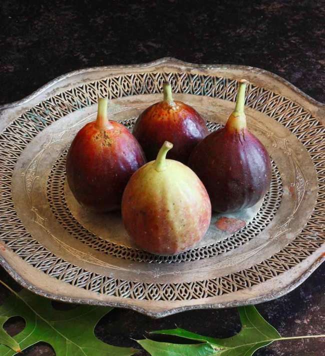 Four Mission figs on a silver platter, to be made into Figs Prosciutto.