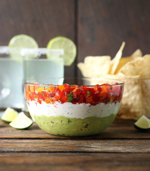 Triple Layer Guacamole Creamy Cotija Confetti Salsa Party Dip in a bowl.