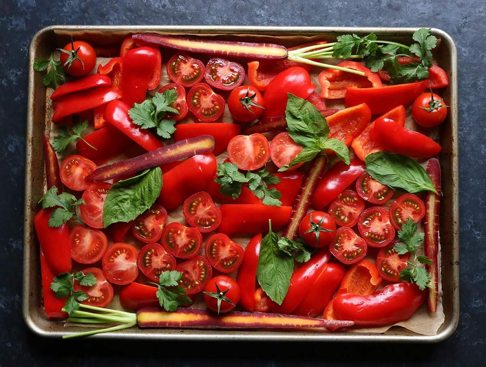 The beautiful red vegetables for Sheet Pan Roasted Red Pepper Tomato Soup spread on a baking sheet