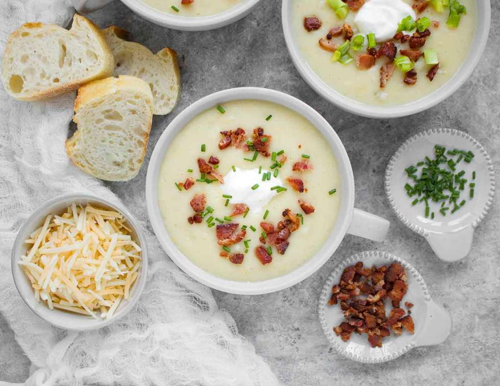 Bowl of Instant Pot Loaded Potato Soup with garnishes