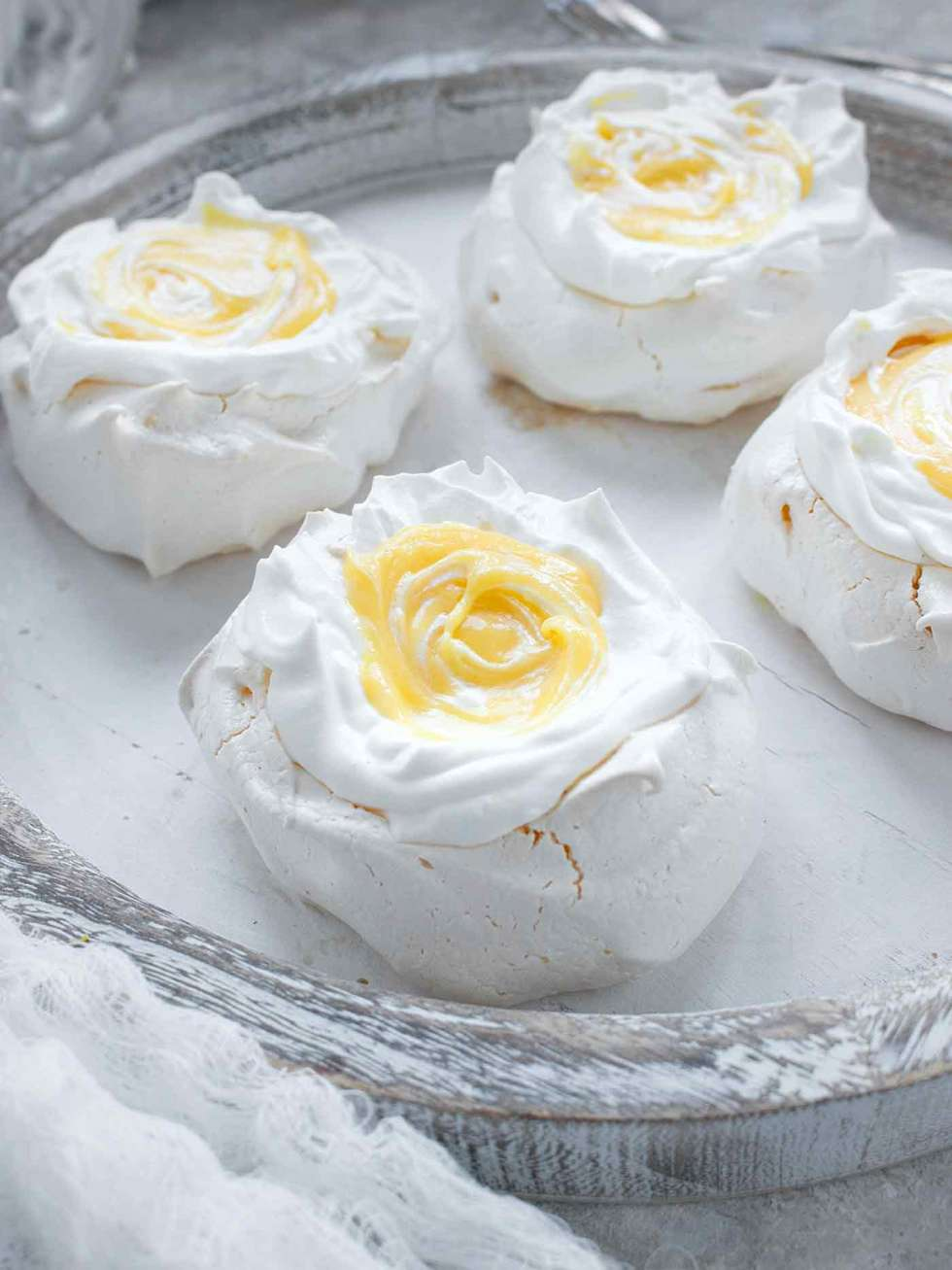 Mini pavlova with tangerine curd on a white serving board