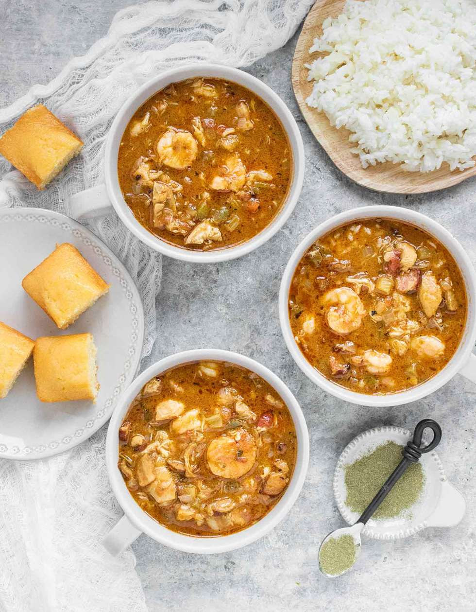 Three bowls of chicken seafood sausage gumbo, with a side of rice and cornbread, plus file powder