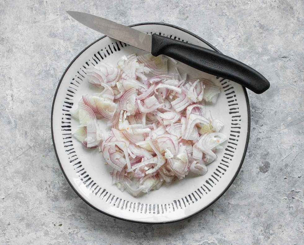Sliced shallots on a plate with a paring knife