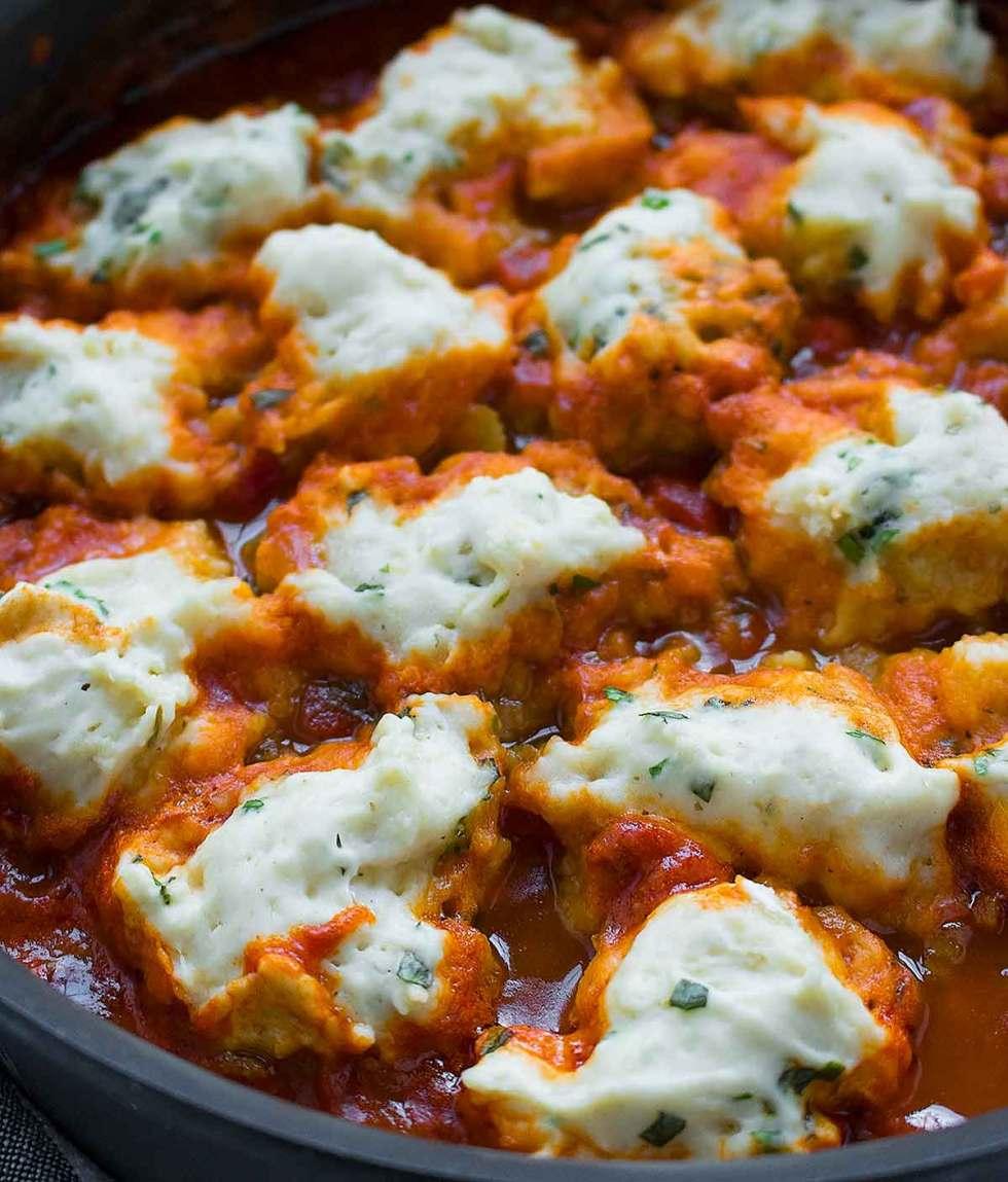 Vegan dumplings cooking in vegetable soup.