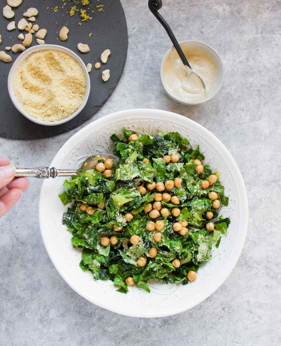 Tossing vegan caesar salad in a bowl