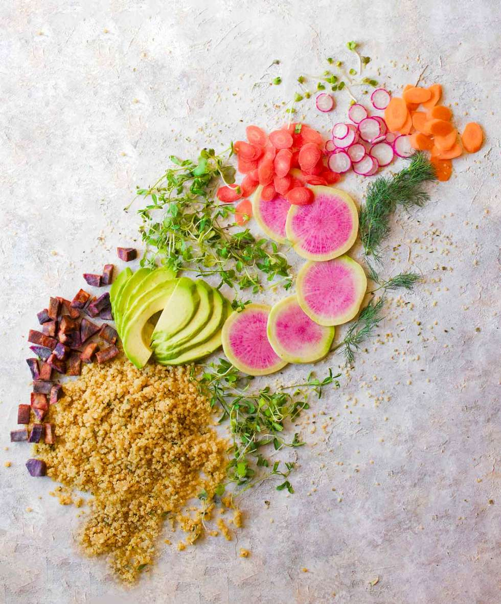 Ingredients for a vegan buddha bowl, spread across a table in a rainbow