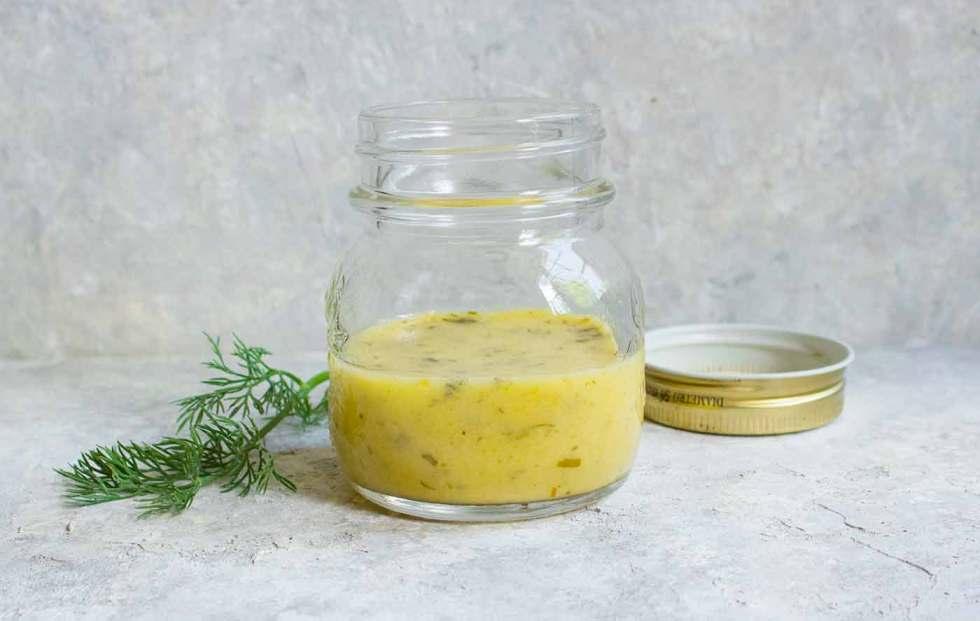 A jar of homemade lemon dill dressing for the Summer Cauliflower Power Salad