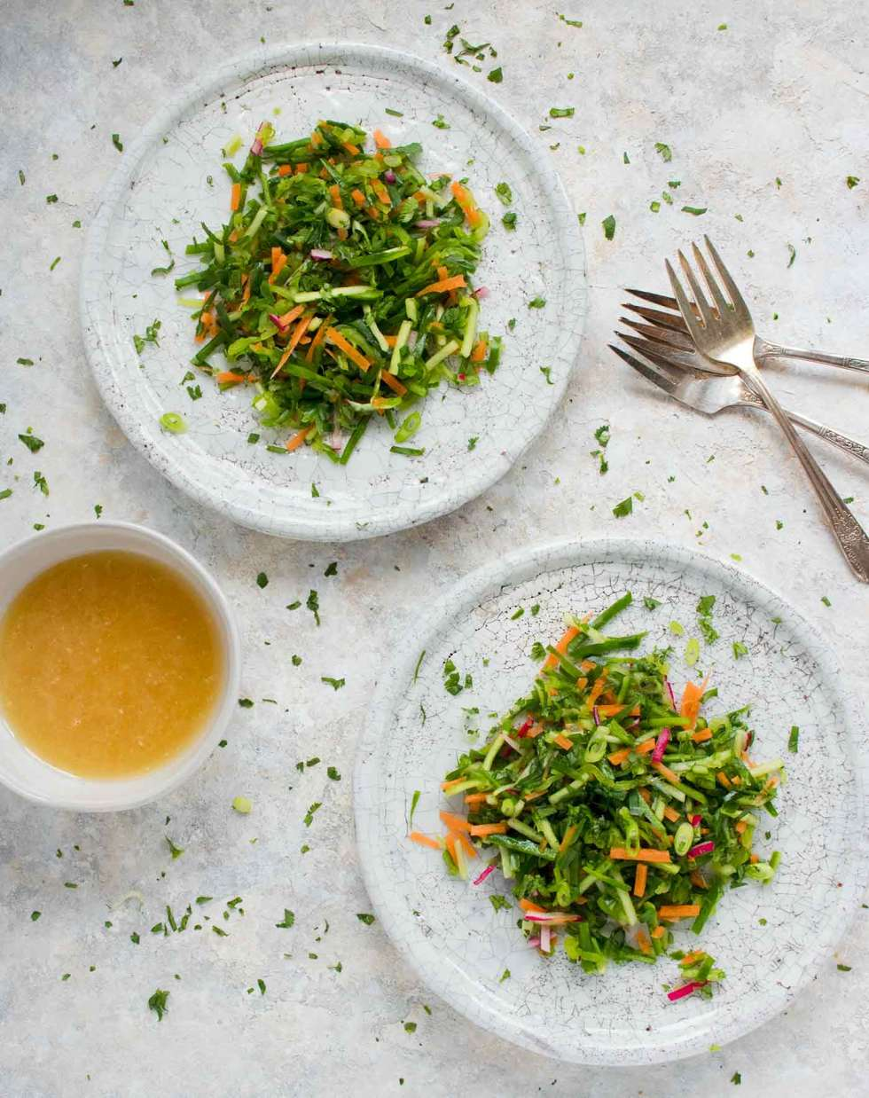 Two plates of cucumber slaw with Asian dressing on the side