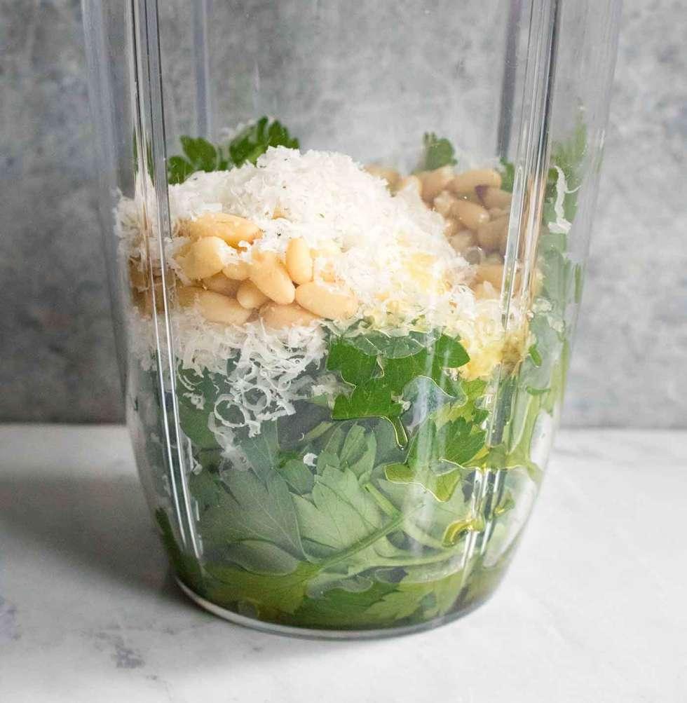 Ingredients for parsley pesto in a blender jar