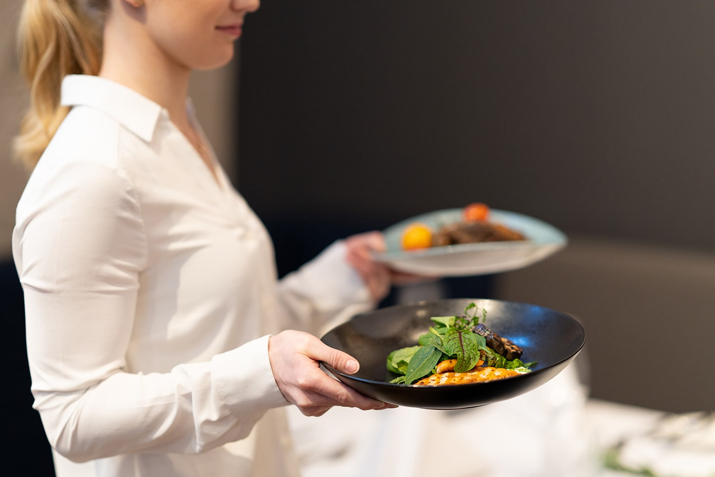 junge Frau bringt Teller mit kleinen Gerichten