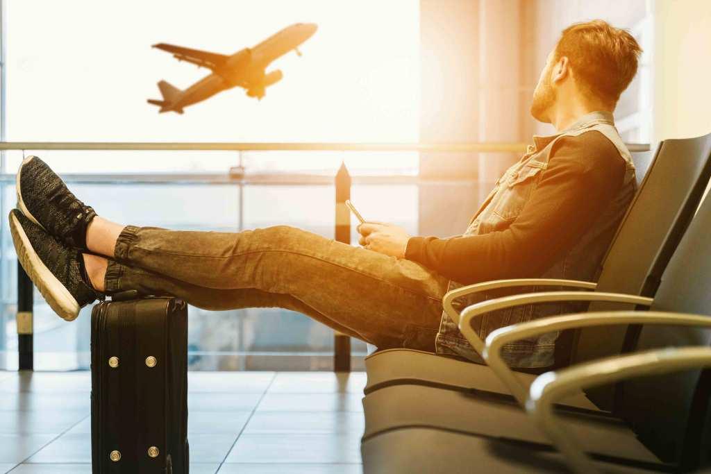 Homem jovem com bagagem no aeroporto