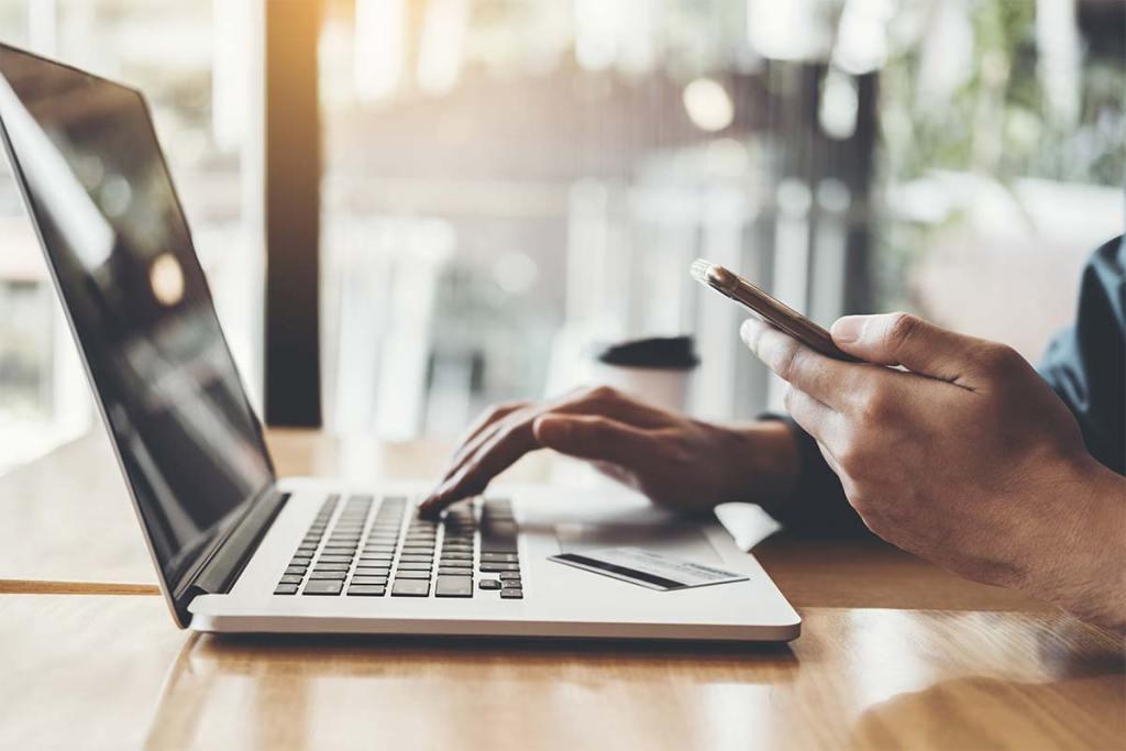 Homem usando laptop com cartão de crédito