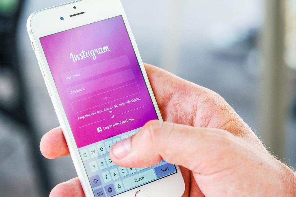 Mão a segurar no smartphone com o login de instagram