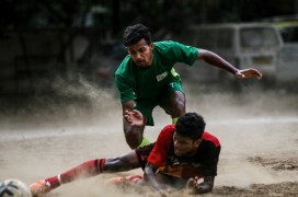 A player is tacked as he falls to the ground trying to reach for the ball during a match, Mumbai, India.
