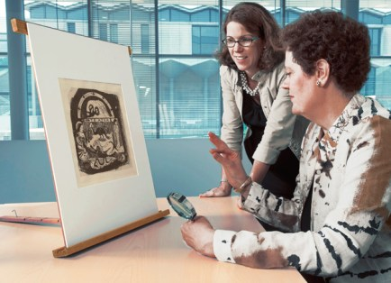 Childs, also associate professor of art history & archaeology, confers with Kate Butler, PhD, assistant curator of the Mildred Lane Kemper Art Museum, on Gauguin's woodcut, Te Atua. (David Kilper)