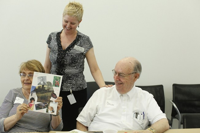 From left to right: Afra Jean Walker displays her art work as Allison Taylor and Walker's husband, Douglas, look on. (Photo: Whitney Curtis/Washington University)