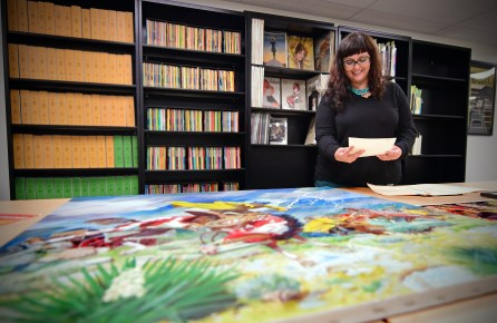 Skye Lacerte, the curator of the Modern Graphic History Library Curator, inspects the Walter Baumhofer Collection. (James Byard/WUSTL Photos)