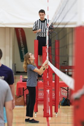 Intramural sports supervisor Sarah Taylor, a senior studying Spanish and urban studies, sets up a volleyball net for the first intramural volleyball game of the season. (Dan Donovan/Washington University)