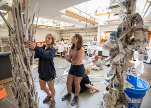 two women in shorts and sneakers affix pieces of rolled-up newspaper to a ceiling-high newspaper sculpture.