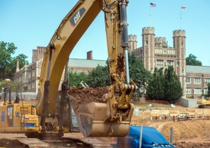 a digger claw lifts dirt in front of Brookings Hall