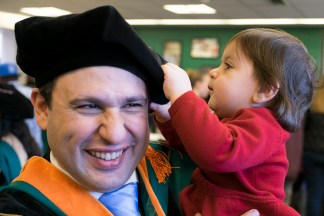 child with dad in graduation gown