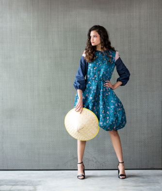 """Michaela Bartley wears a silk cocktail dress by Sherry Yunhui Xu, from Xu's thesis collection """"Oriental Rhapsody."""" Inspired by the collision between Eastern and Western cultures, the collection includes """"floral prints featuring cherry blossom and morning glory [as] my tributes to my Chinese cultural heritage,"""" Xu explains, as well as bold and voluminous silhouettes reflecting """"the Western idea of being avant-garde and standing out from the crowd."""" (Photo: Jennifer Silverberg/Washington University)"""