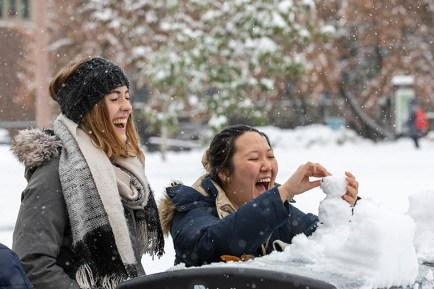 Students Giulia Neaher (left) and Phoebe Li build a snowman as snow falls Nov. 15 on the Danforth Campus. (Photo: Joe Angeles/Washington University)