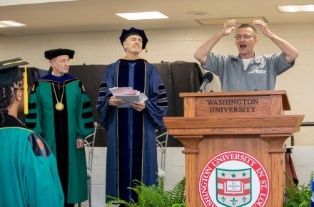 "(From right:) Stanley Cook sings ""America the Beautiful"" while Robert Henke and Chancellor Mark S. Wrighton look on."